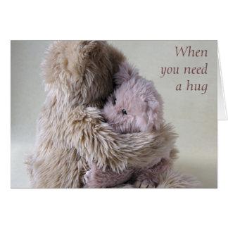 big teddy bear holds little bear card hug
