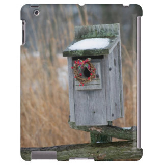 Bird, nest box with holiday wreath in winter