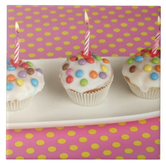 Birthday muffins with icing, sprinkles and ceramic tile