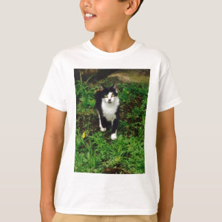 Black and white tuxedo cat in the green grass T-Shirt