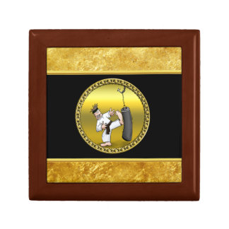 Black belt karate man kicking a black training bag gift box