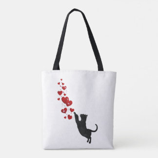 Black cat plays with red hearts tote bag