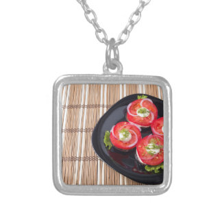 Black dish with sliced tomatoes and lettuce silver plated necklace