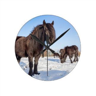 Black frisian horses in winter snow round clock