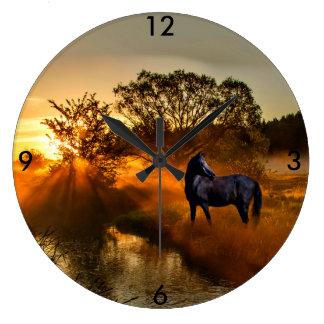 Black horse at sunrise or sunset large clock