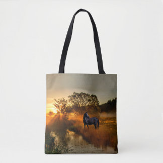 Black horse at sunrise or sunset tote bag