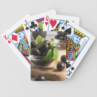 Black olives in a glass bowl on the old vintage bicycle playing cards