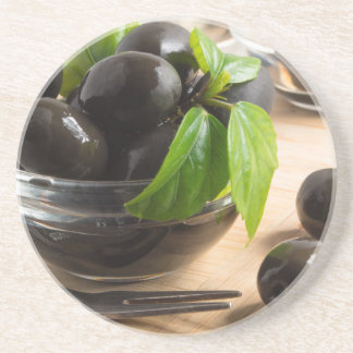 Black olives in a glass bowl on the old vintage coaster
