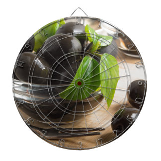 Black olives in a glass bowl on the old vintage dartboard