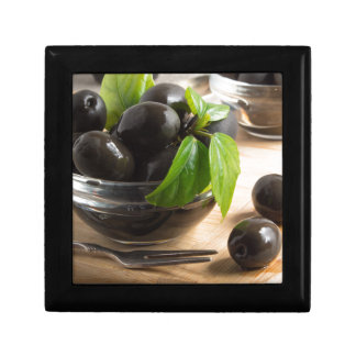 Black olives in a glass bowl on the old vintage gift box