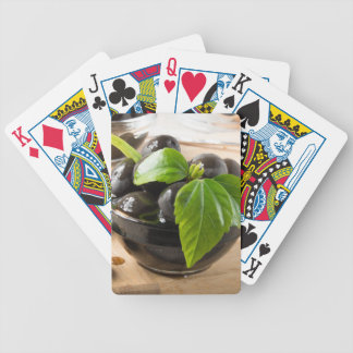Black olives on a table and glass cups with oil bicycle playing cards