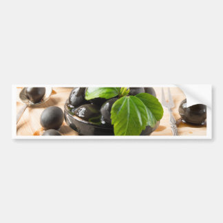 Black olives on a table and glass cups with oil bumper sticker