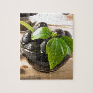 Black olives on a table and glass cups with oil jigsaw puzzle