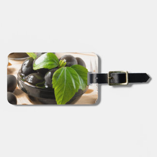 Black olives on a table and glass cups with oil luggage tag