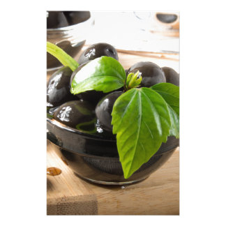 Black olives on a table and glass cups with oil stationery