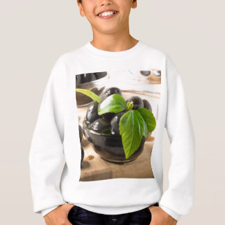 Black olives on a table and glass cups with oil sweatshirt