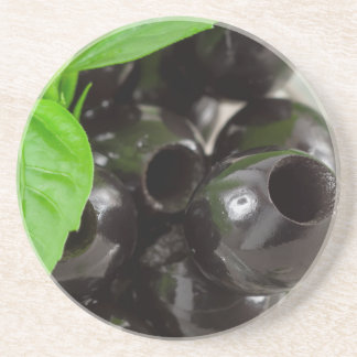 Black olives, pitted marinated in a glass bowl coaster