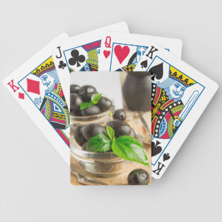 Black olives with green leaves with vintage bicycle playing cards