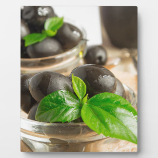 Black olives with green leaves with vintage plaque