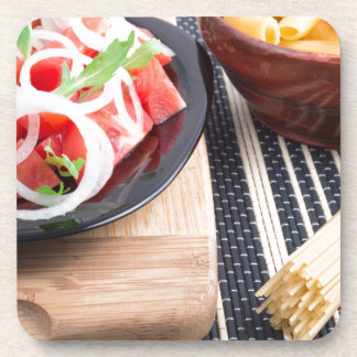 Black plate with fresh salad of tomatoes, onions coaster