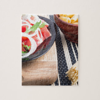Black plate with fresh salad of tomatoes, onions jigsaw puzzle