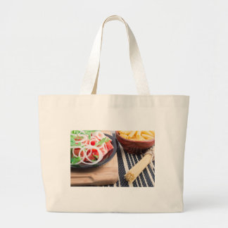 Black plate with fresh salad of tomatoes, onions large tote bag
