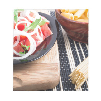 Black plate with fresh salad of tomatoes, onions notepad