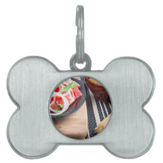 Black plate with fresh salad of tomatoes, onions pet name tag