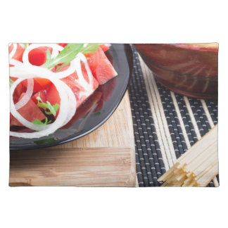Black plate with fresh salad of tomatoes, onions placemat