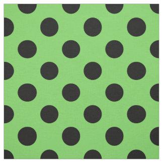 Black polka dots on lime green fabric