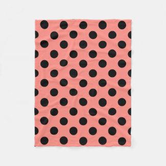 Black polka dots on peach fleece blanket