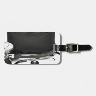 Black professional blood pressure monitor on white luggage tag