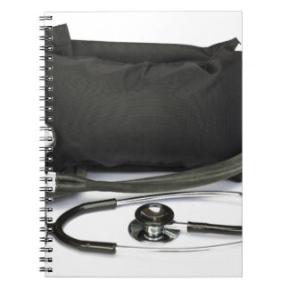 Black professional blood pressure monitor on white notebook