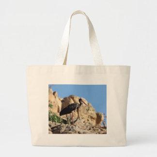 Black stork (Ciconia nigra) on a rock. Large Tote Bag