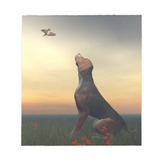 Black tan dog looking a bird flying notepad