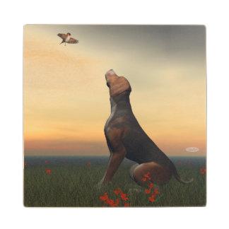 Black tan dog looking a bird flying wood coaster