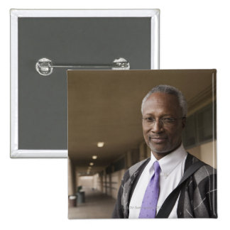 Black teacher standing in school corridor 15 cm square badge