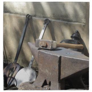 Blacksmith hammer resting on the anvil napkin