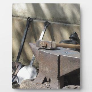 Blacksmith hammer resting on the anvil plaque