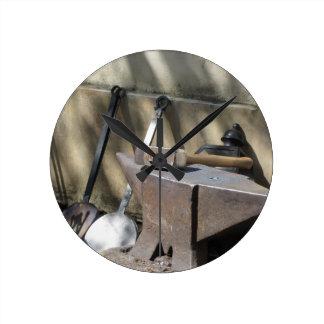 Blacksmith hammer resting on the anvil round clock