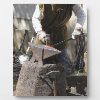 Blacksmith manually forging the molten metal plaque