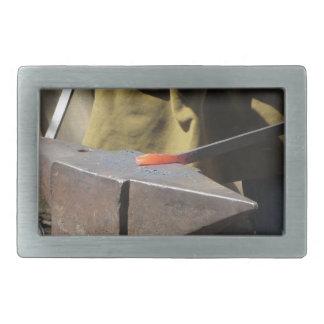 Blacksmith manually forging the molten metal rectangular belt buckle