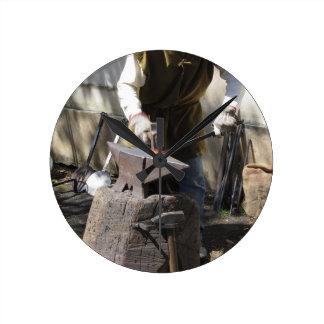 Blacksmith manually forging the molten metal round clock