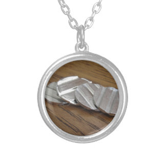 Blank metallic coins on wooden table silver plated necklace