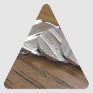 Blank metallic coins on wooden table triangle sticker