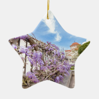 Blooming blue Wisteria sinensis on fence in Greece Ceramic Star Decoration