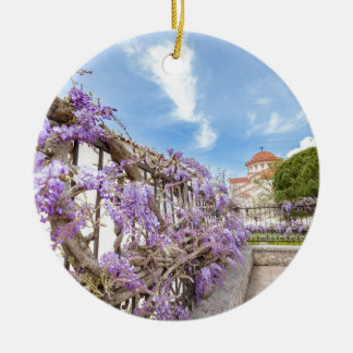 Blooming blue Wisteria sinensis on fence in Greece Round Ceramic Decoration