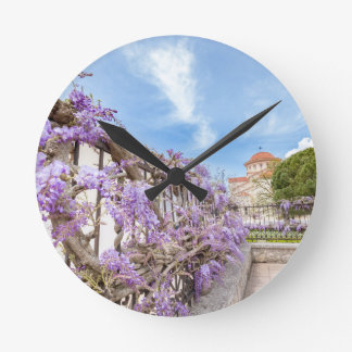 Blooming blue Wisteria sinensis on fence in Greece Round Clock