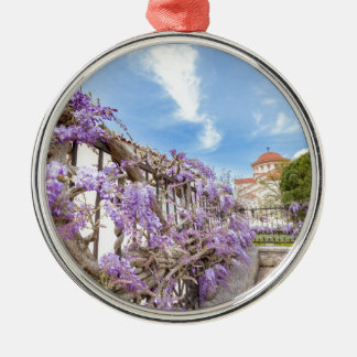 Blooming blue Wisteria sinensis on fence in Greece Silver-Colored Round Decoration