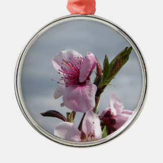 Blossoming peach tree against the cloudy sky metal ornament